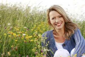 middle aged woman smiling in a field of flowers