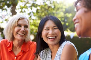 three middle-aged women laughing outdoors