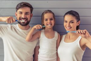 young parents and their cute little daughter are looking at camera and smiling while brushing teeth focusing on preventative dentistry in Greensburg, PA